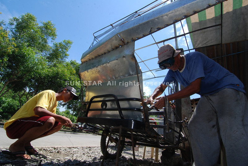 DAVAO. Payong-payong owner Jonard Tolentino watches Sammy Gunab make a close-cab design to replace the payong-payong in a shop along Ecoland Drive Monday. (King Rodriguez)