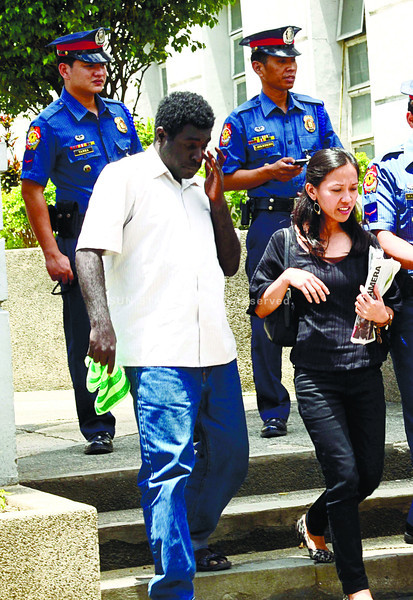 STEP BY STEP. Bennidict Penini (foreground) leaves the Palace of Justice in Cebu City with Swat operatives PO1 Philip James Tanza (background, left) and PO2 Bradford Lavandero. Both parties went to the prosecutor's office yesterday. (Amper Campaña)