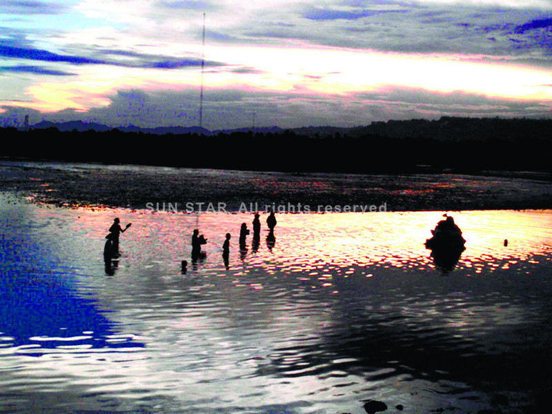 WALKING ON WATER. People living near the South Road Properties take a shortcut through the shallow end of a narrow strip of water that separates the reclaimed area from the original coastline in Barangay Mambaling, Cebu City. (Sun.Star Photo/Allan Defensor)