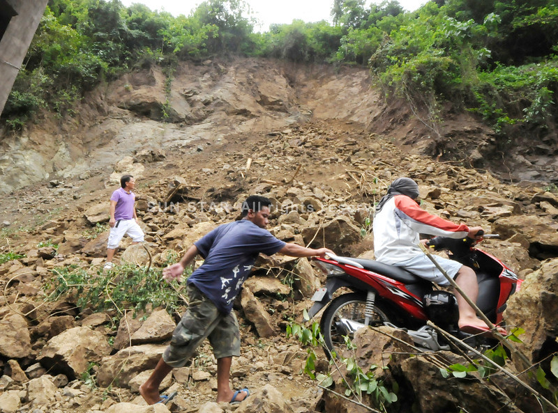 ROCKS THAT ROLLED. Talisay City Councilor Danny Caballero (far right) inspects the damage caused by a landslide in Barangay Campo 4, Talisay City. (Alex Badayos)
