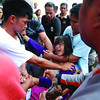 DAVAO. A student is restrained by a faith healer who carries with him a bottle of oil and herbs as students, teachers, and residents had to contend with the hysterics of at least 20 fourth year high school girls of Crossing Bayabas National High School in what is believed to have been a possession of some spirits on Monday. (King Rodriguez)