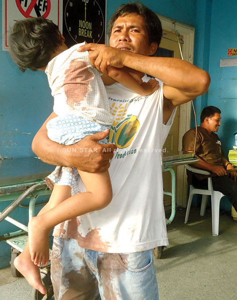 DAVAO. Three-year-old Michael is comforted by his father who was among who were rushed to the Southern Philippines Medical Center for treatment after the grenade explosion in a carnival in Paquibato. (Alger Dura)
