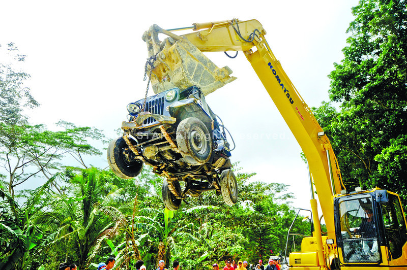 RETRIEVAL.  A back hoe from QM Builders picks up the wreckage of the police service car from the foot of a cliff where it fell last Thursday dawn in Dalaguete.  (Sun.Star Photo/Alex Badayos)