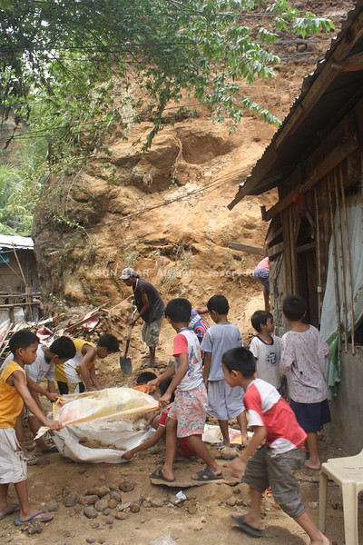 CAGAYAN DE ORO. Residents, including children, work together to clean up the mess where an earthquake-triggered landslide occurred Friday night in Upper Kolambog, Barangay Lapasan that killed Emelita Ubalde and injured her five-year-old grandson Adrian Rosales. (Joey P. Nacalaban)
