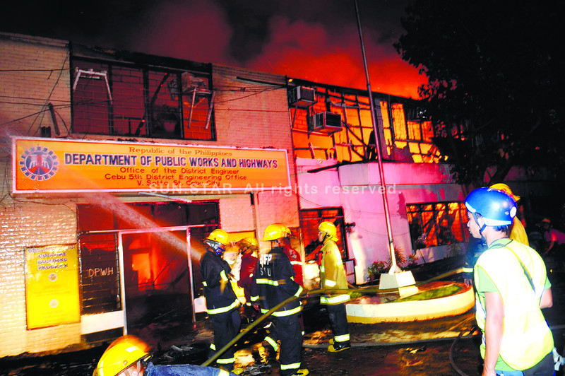 AFTER OFFICE HOURS.  Firefighters and a thick wall kept the flames from crossing to a building next-door, but a fire destroyed this Department of Public Works and Highways office in Cebu City's pier area.  (Sun.Star Photo/Allan Cuizon)