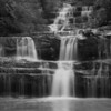 "N grade Open........""Terrace Falls"" by jacqui Scott""........Merit<br /> <br /> A very nice effort, well exposed and a good use of a closed aperture...f22 plus I'm guessing and its also a nice conversion to black and white . There is a bit of a burn out in the water particularly at the bottom but its still a well handled shot. I would also use the dodge tool to brighten up the image away from the central waterfall and then use curves to finish the photo off.<br /> To give you an example of what you can do, I opened this in Photoshop and checked out the curves and found that there was a bit of a gap on the right of the curve so pushed the bottom slider left to cut this out and it made the image ""pop"". You can also do more to pop the image by judicious use of the unsharp mask tool. The trick with all of these techniques is to do it in Photoshop before converting or saving as the final jpeg image, otherwise you lose too much data and the image downgrades.<br /> A good merit."