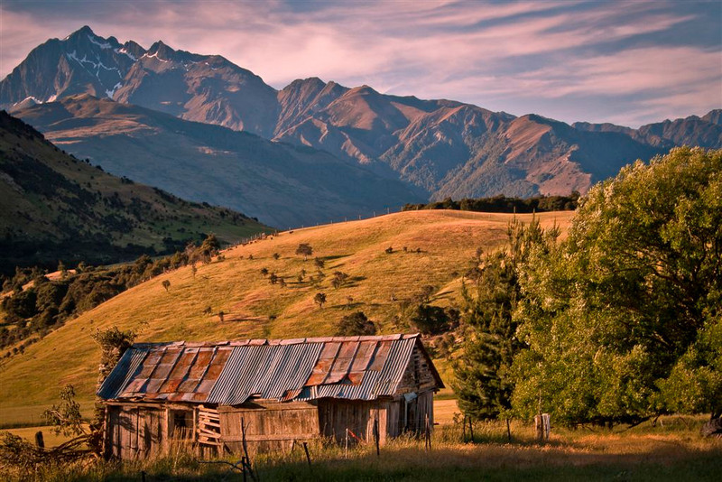 """A grade open........"""" The Old Hut """"  by  Jacquie Scott........Honours.<br /> <br /> This is a beautiful image with lovely low lighting. Although the old hut is the focal point, the surrounding landscape plays a huge part here with the low sunlit hill contrasting with the rugged mountains behind. The sunlit hill leads the eye from the old hut diagonally across the image and up into the beautiful sky. I like the way the dark hill on the left and the tree on the right frame the hut and the light hillside. The shadow across the foreground holds the base of the image in. Superb composition creating a wonderful landscape."""