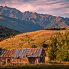 "A grade open........"" The Old Hut ""  by  Jacquie Scott........Honours.<br /> <br />  This is a beautiful image with lovely low lighting. Although the old hut is the focal point, the surrounding landscape plays a huge part here with the low sunlit hill contrasting with the rugged mountains behind. The sunlit hill leads the eye from the old hut diagonally across the image and up into the beautiful sky. I like the way the dark hill on the left and the tree on the right frame the hut and the light hillside. The shadow across the foreground holds the base of the image in. Superb composition creating a wonderful landscape."