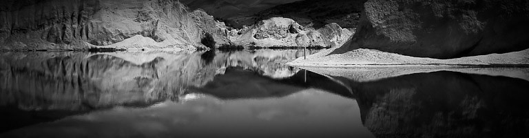 """Novice grade open........"""" St Bathans """"  by  Linda Ferrier........Merit.<br /> <br /> I love the monochrome, you have a good range of blacks and whites without losing the detail in the whites. The  panorama format suits this scene. I like the way you cropped this so that the bottom part is greater than the top. Having spent many hours at St Bathans, over the years, I know how difficult it is to decide which part of the lake to include in your image. I wonder if the RH scree  intrudes on the rest of this image. The more I look at it , the more I see two images. Perhaps it is the heavy black hill and shadow on the RH side that take up ¼ of the image where as all the rest of the cliffs are light. The balance of this, just stops it from being an honours."""