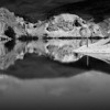 "Novice grade open........"" St Bathans ""  by  Linda Ferrier........Merit.<br /> <br /> I love the monochrome, you have a good range of blacks and whites without losing the detail in the whites. The  panorama format suits this scene. I like the way you cropped this so that the bottom part is greater than the top. Having spent many hours at St Bathans, over the years, I know how difficult it is to decide which part of the lake to include in your image. I wonder if the RH scree  intrudes on the rest of this image. The more I look at it , the more I see two images. Perhaps it is the heavy black hill and shadow on the RH side that take up ¼ of the image where as all the rest of the cliffs are light. The balance of this, just stops it from being an honours."