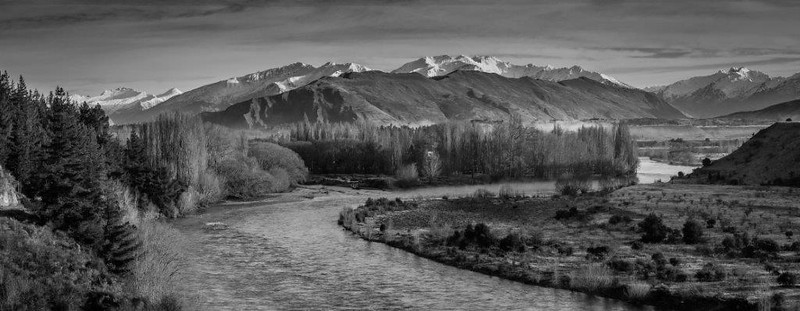 The Clutha river Jacquie Scott A<br /> Beautiful moody landscape in which the eye travels comfortably along the bend of the river to the point of the tree line and then to the mountains beyond.  Although there is no dramatic lighting the monochromatic treatment presents us with a different take on the landscape.  Well seen and presented.  Simple but effective composition. Merit