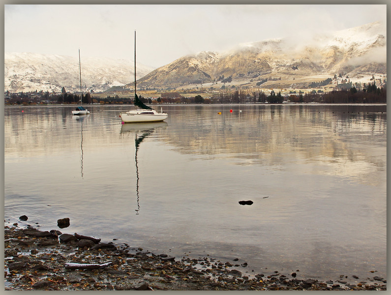 First Touch of Winter  -  Barbara Lee<br /> A stylish and well composed image, making good use of the rule of thirds.<br /> The rocky foreground material serves nicely as an anchor point which is then counterbalanced by the mountain ranges in the background.<br /> The boats on the lake are perfectly positioned and their full reflections provide the viewer with strong vertical lines, in contrast with the horizontal landscape. <br /> The atmosphere is one of stillness and reflective contemplation and I very much enjoy the understated colour tones.<br /> My only criticism is that, within these muted tones, we see the more colourful buoys on the lake, and even though they are very small, they nonetheless draw my attention. Try to de-saturate these so they are more in keeping with the rest of the image. Honours