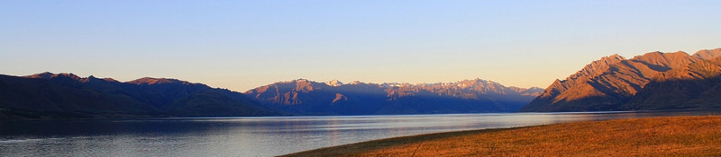 Lake Hawea  -  Amy Ballantyne<br /> A pleasing panorama shot. The foreground curve moving in from the right is nicely counterbalanced by the sweep of the lake.<br /> Darker mountain ranges at the edges of the image also help to contain the viewer within the picture and the colour tones of gold and blue complement each other well.<br /> The image works nicely in horizontal thirds: foreground and lake, followed by mountains and finally sky. Accepted<br /> I feel the sky is the weakest part of the image and could possibly be darkened down nearer the top of the frame to help contain the viewer in the bottom half of the picture.