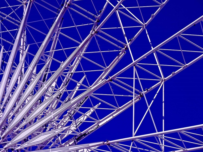 Surfers Ferris Wheel   -  Rebecca Campbell<br /> The abstract quality is very appealing in this arresting image, and the author has done well to isolate part of a scene rather than attempting to include the whole.<br /> The starkness of the white and blue is very effective and highlights the architectural construction and geometric patterning.<br /> Strong diagonals from the bottom left corner carry through the shot but are nicely counterpointed with the many horizontal struts forming mini-squares and smaller triangles. Compositionally, I'd suggest making a horizontal flip – this way, when we read left to right, the stronger white diagonal lines will push the viewer back into the image, whereas in its current orientation, it's easier to be lead out of the picture. Accepted