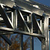 Steel Truss in Reflected Light   -  Rod Macleod<br /> I can see why the author was drawn to this scene as the light on the metal is very attractive.<br /> Unfortunately, I feel too much has been included in the image, particularly the out of focus trees in the background.<br /> Also, the approach to the shot has been rather literal and static – there is a great opportunity here to explore the geometric shapes and patterns with a less conventional approach.<br /> If you can go back to this scene, try to get in closer and really exploit the cross diagonals and recurring patterns to create a more 'dynamic' and dramatic image. Not Accepted