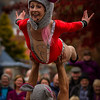 Street Theatre – The Acrobat  -  Allen Hogan<br /> This image made me smile and is very deftly handled.<br /> Great use of selective focus immediately draws our attention towards the performers, yet the background is not so blurred out that we can't make out the joyous expressions on the faces in the crowd behind.<br /> This gives us a real connection to the events taking place and makes us feel participants in the fun.<br /> The performer's face is beautifully sharp, as is the detailing on her costume, and the colour palette of the image is rich and warm. <br /> My only suggestion would be to perhaps lighten the area around the subject's face to differentiate her even more from the darker background behind.<br /> A great PJ shot, vibrant and very appealing – well captured. Honours