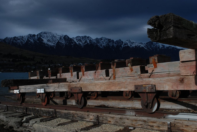 Remarkable Queenstown Allan Ford A grade<br /> This is an interesting image with a moody atmosphere. The light on the rail wagon contrasts with the dark mountains and overcast sky. I find the composition doesn't sit comfortably with me. I wonder if you decided to flip the image and had the larger timber on the RH side, would that work better.ACC