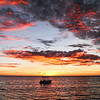 Summer Sunset  -  Nick Wallis<br /> Your wise title tells us that it was Summer ,otherwise it could be any season of the year as we get sunsets like this all year round. I like the vertical format, I think it works well. You have perhaps placed the boat too much in the centre of the image perhaps a little to the left would have given you a better balance. I like the bands of shoreline at the bottom and those moody clouds at the top, they hold the image together. Novice Merit