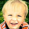 Squinty McSquinston - Bevin Young<br /> A lovely natural child study, very vibrant and eye catching. You could have had a wee bit more space below his chin but otherwise a great shot .If you work on the computer you could clone out the white spots in the background as they are distracting. Novice Merit