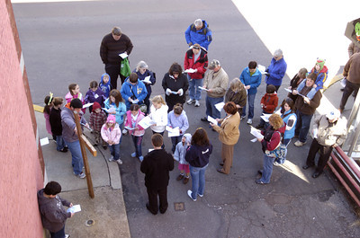 A crowd gathers in front of a cross on Mill Street in Danville on Friday during a cross walk.