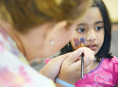 Brittany Mull paints the face of Swecha Mamillapalli, 3, during the Danville Child Development Center carnival on Thursday morning.