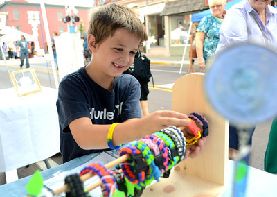 Ryan Prall, 6, of Riverside picks out a paracord bracelet at one of the booths lining Mill Street Saturday Sept. 8, 2012 during Danville's annual Fall Arts and Crafts Festival.