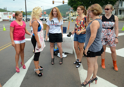 Competitors in the Stilleto Stampede react to the news they will be running almost a quarter mile up Mill Street in Danville Saturday morning Sept. 8, 2012.  More than a dozen women and men raced in at least three inch heels to raise money for the Danville Area Community Center.