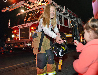 Emily Burkland, of Riverside, hands a piece of candy to Norah Levan, 2 of Berwick, during the Danville Halloween Parade on Thursday night.