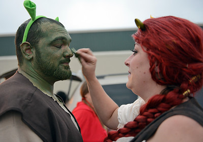 "Lauren Reedy, of Danville, puts green makeup onto her husband Dean's face before the Danville Halloween Parade on Thursday night. The couple dressed as Shrek and Fiona as part of the family float themed ""Once Upon a Time."""