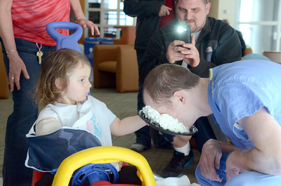 Mariah Silverman, 3, puts a pie into the face of pediatric resident Lukasz Weiner, as her father Jay Silverman takes a photo during a Child Life Week activity on Friday at the Janet Weis Children's Hospital.