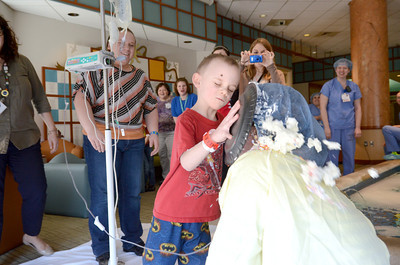 Trenton Dawson, 7, Covington, puts a whipped cream pie in the face of Geisinger pediatric resident Jessica Nelson on Friday to close out Child Life Week at the Janet Weis Children's Hospital in Danville.