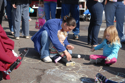 Jessica Kerichan helps Serenity Bardo, 1, color with chalk next to Laila Wolfe, 3, Danville, at the Easter egg hunt on Saturday at Grandview Health Homes.