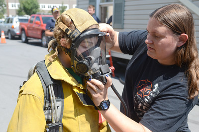 Katelyn Beck, 12, left, gets help putting on a fire figther mask from Elizabeth Stigerwalt at a fire fighter summer camp in Danville on Friday.