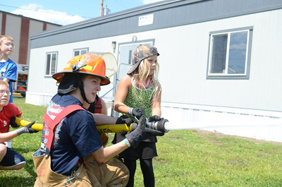 Junior fire fighter Ryan Potopsky, left, helps Bryanna Kipple,10, control a hose on Friday afternoon in Danville during a fire fighter summer camp.