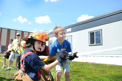 Junior fire fighter Ryan Potopsky, left, helps Evan Thomas, 9, control a hose on Friday afternoon in Danville during a fire fighter summer camp.