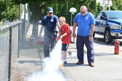 Fire fighters Mike Kull, left, and Keith Rine, right, help Dakota Rathburn, 10, operate a fire extinguisher on Friday in Danville during a fire fighter summer camp.