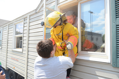 Cody Foust, left,and Jesse Carl, right, help Bryanna Kipple, 10, through a window after making her way through a smoke house on Friday in Danville during a fire fighter summer camp.
