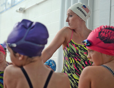 Heather Galio, 8 of MacUngie, and another swimmer practice a backstroke technique shown to them by Olympic swimmer Claire Donahue during the Fitter and Faster Swim Tour at the Danville Area Community Center on Saturday afternoon.