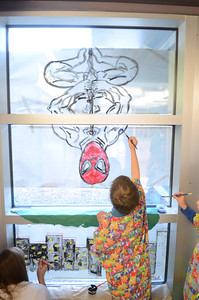 Danville Primary first grade student Andy Donahue, 6, reaches up to paint Spiderman's arm on a window at the Danville Primary School on Tuesday.