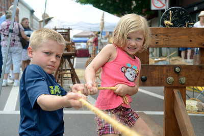Siblings, Ty, 6, and Lea Hall, 4, of Danville finsih off their rope with a stong stretch at a rope making demonstration with Rich Nornhold of Watsontown during Danville's Iron Heritage Festival Saturday July 21, 2012.