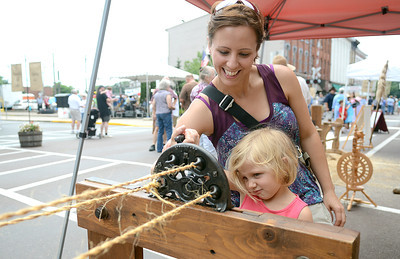 Lea Hall, 4, of Danville spins some twine with her mother, Jamie, to make rope at the booth of Rich Nornhold of Watsontown along Mill Street during the Iron Heritage Festival Saturday July 21, 2012.