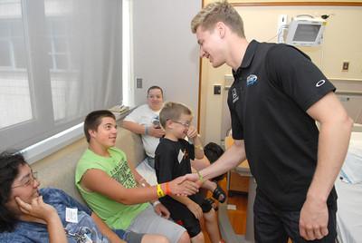 Janet Weis Children's Hospital patient Ryan Ellsworth, left, shakes hands with Indy car driver Josef Newgarden, right, while his mother Cathy, and brother Josh, watch on Friday morning as part of a Racing For Kids charity.
