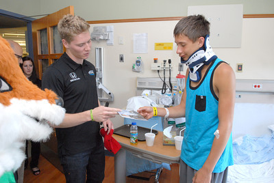 Indy car driver Josef Newgarden, left, hands a signed photo to Janet Weis Children's Hospital patient Christian Karek, Lancaster NY, while visint the hospital on Friday as part of the Racing For Kids charity.