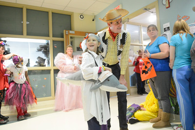 Adelaide Kanton, 7, Scranton, smiles with Bucknell men's basketball assistant coach Kevin Snyder at the Janet Weis Children's Hospital on Friday as patients went trick or treating.