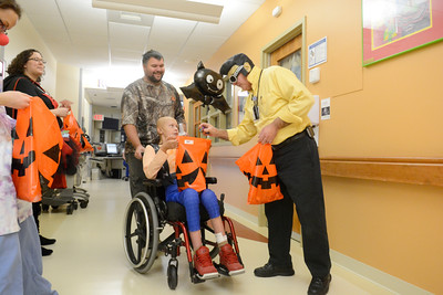 Walter Dickerson, left, of Ridgebury pushes around Dakota Wade, 11, as they get a Halloween treat from Steve Zeiders, at the Janet Weis Children's Hospital on Friday.