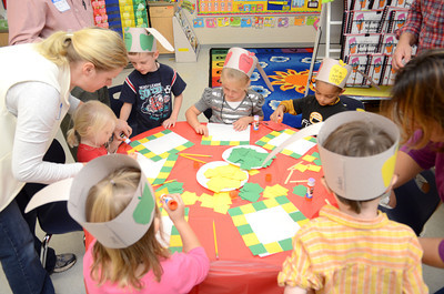 Kindergarten students in June Heeter's class get some help with a craft project as they celebrated Johnny Appleseed Day at the Danville Primary Center.