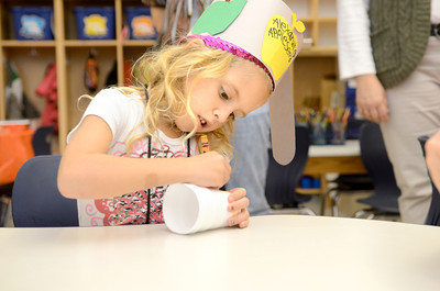 Alexandra Romanot decorates a cup that will be used to plant an apple seed in June Heeter's kindergarten class at the Danville Primary Center as they celebrated Johnny Appleseed Day.