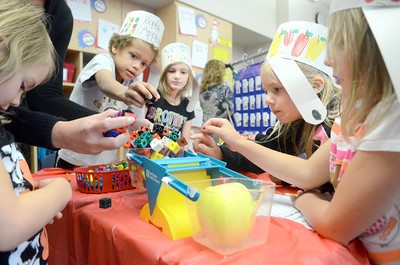 Danville Primary School first grade students Sophie Stobo, left, Shannon Ernest, Ella Meadows, and Lila Ross, find out how many blocks an apple weighs during a class lesson on Wednesday on apples and Johnny Appleseed.