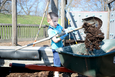 Garrett VonBlosh, 4, Danville, puts a shovel full of dirt in a wheel barrow while helping fix up the Kidsville playground in Danville on Sunday.