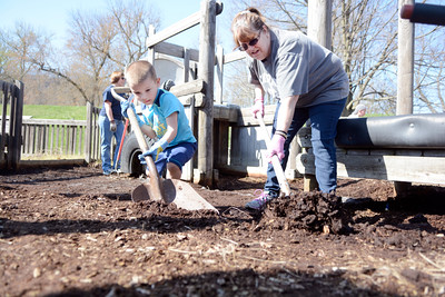 Garrett VonBlohn, 4, and his grandmother Deb VonBlohn, Danville, shovel dirt to make room for new mulch at the Kidsville playground in Danville on Sunday.